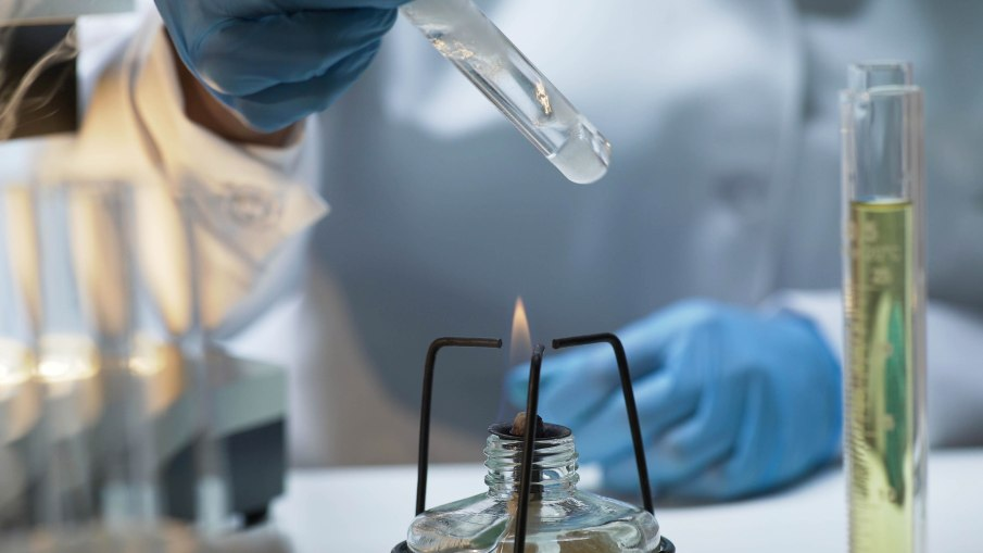 Scientist holding tube with boiling fuming liquid over burner, lab experiment